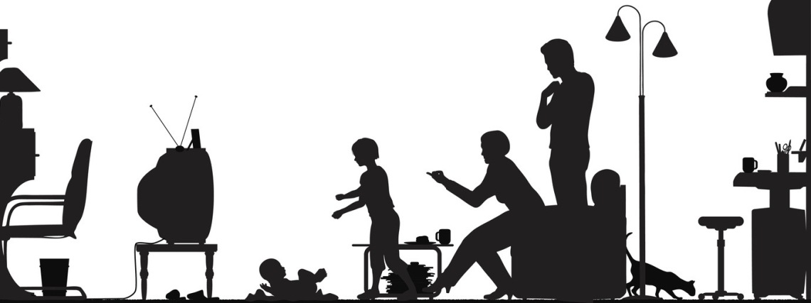 Silhouette of a family with a baby watching television
